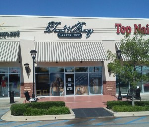 A photograph of a tanning salon logo sign after installation.